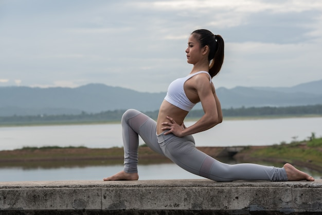 Trägt die jungen frauen zur schau, die morgens yoga durch das reservoir mit gebirgshintergrund üben. Premium Fotos