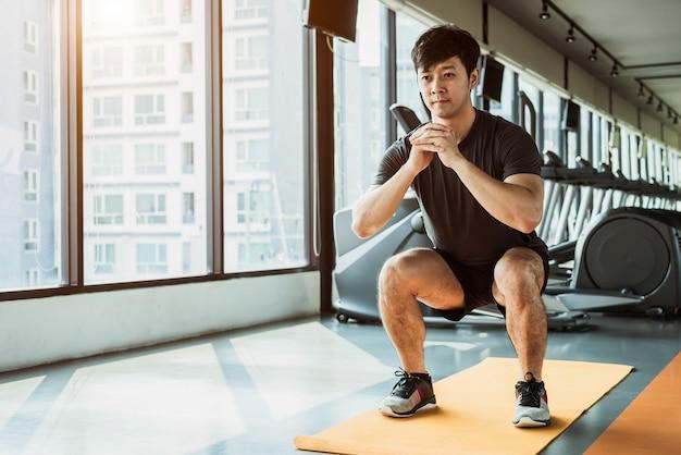 Tragen sie den mann zur schau, der hockenlage auf yogamatte in der eignungsturnhalle am kondominium in städtischem tut Premium Fotos