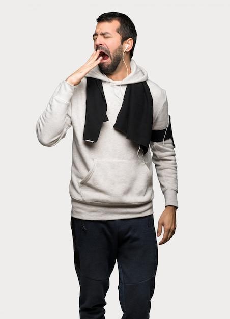 Tragen sie den mann zur schau, der weit offenem mund mit gähnendem und überdeckendem grauem hintergrund gähnt Premium Fotos