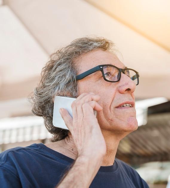 Tragende brillen des älteren mannes, die auf smartphone sprechen Kostenlose Fotos