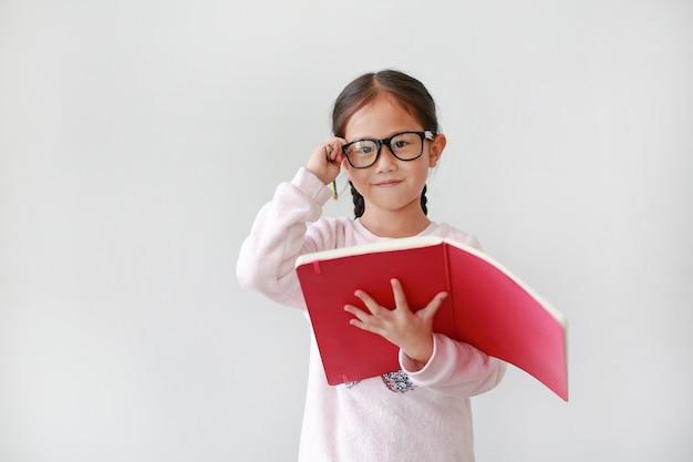 Tragende brillen des asiatischen schulmädchens und halten des notizbuches mit bleistift auf weiß. Premium Fotos