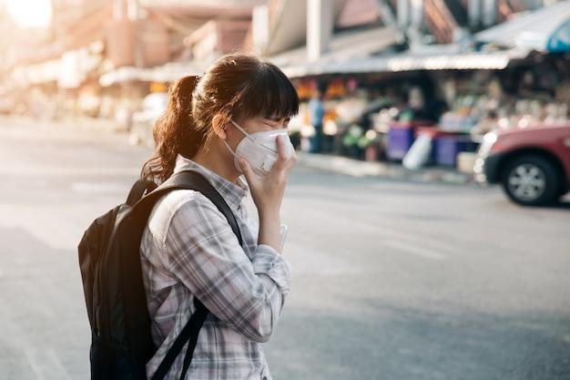 Tragende gesichtsmaske der asiatin, die wegen der luftverschmutzung in der stadt husten Premium Fotos