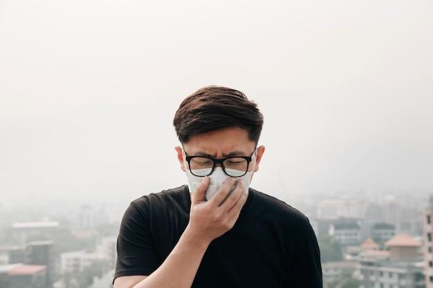 Tragende gesichtsmaske des asiatischen mannes wegen der luftverschmutzung in der stadt. Premium Fotos
