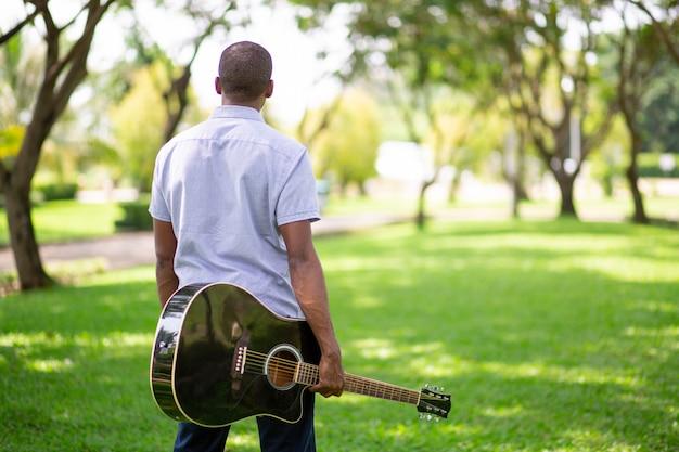 Tragende gitarre des schwarzen mannes im park Kostenlose Fotos