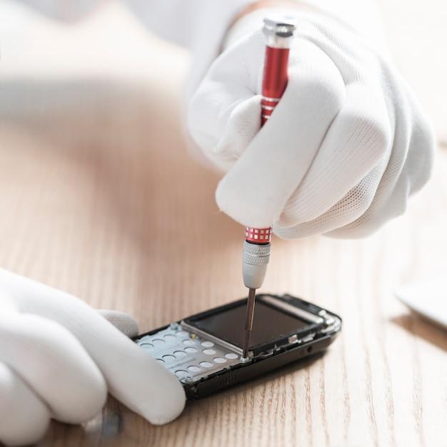 Tragende handschuhe des männlichen technikers, die mobiltelefon reparieren Kostenlose Fotos