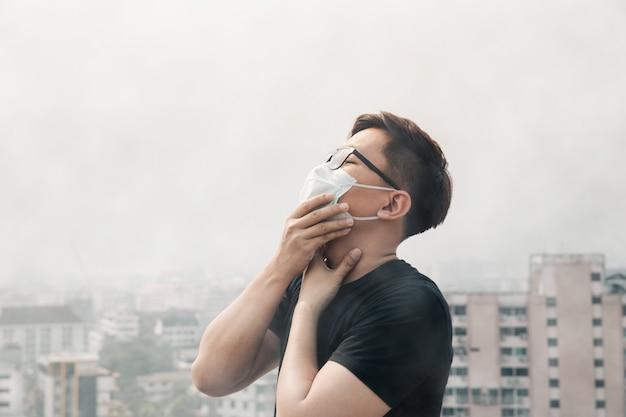 Tragende hygienemaske des asiatischen mannes und krank wegen der luftverschmutzung in der stadt. Premium Fotos