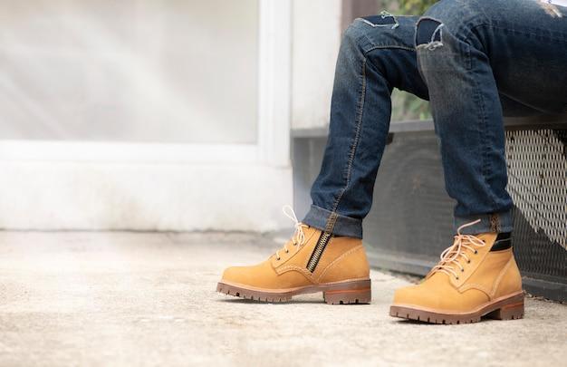 Tragende jeans des mannmodells und braune lederstiefel Premium Fotos