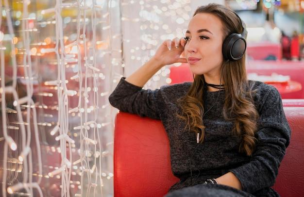 Tragende kopfhörer der frau, die weihnachtslichter betrachten Kostenlose Fotos