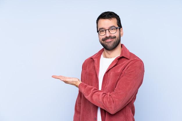 Tragende kordjacke des jungen kaukasischen mannes über der blauen wand, die eine idee beim schauen in richtung lächelt darstellt Premium Fotos