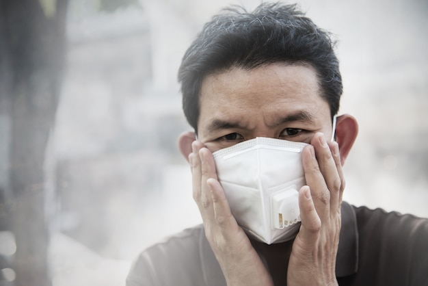 Tragende maske des mannes schützen feinstaub in der luftverschmutzungsumwelt Kostenlose Fotos