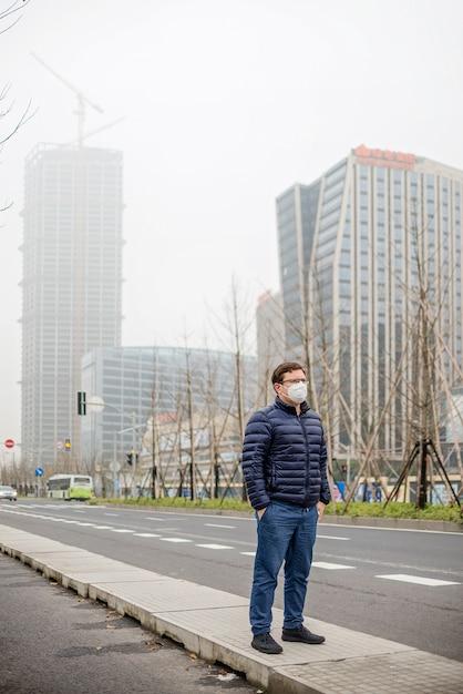 Tragende mundmaske des jungen mannes gegen luftverschmutzung oder coronavirus. lungenentzündungsepidemie Premium Fotos