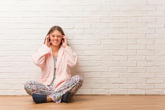 Tragende pyjama-bedeckungsohren der jungen frau mit den händen Premium Fotos