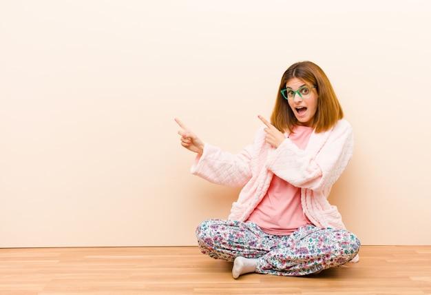 Tragende pyjamas der jungen frau, die zu hause fühlen froh und überrascht sitzen, mit einem entsetzten ausdruck lächeln und auf die seite zeigen Premium Fotos