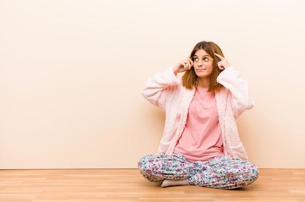 Tragende pyjamas der jungen frau, die zu hause fühlen verwirrt oder zweifelnd sitzen, sich auf eine idee konzentrieren, stark denken und schauen zum copyspace auf seite Premium Fotos