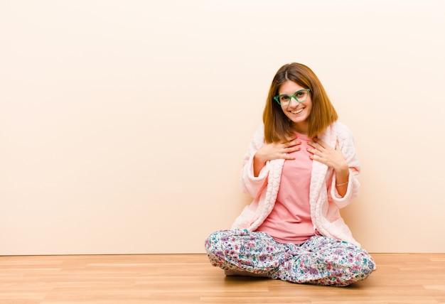 Tragende pyjamas der jungen frau, die zu hause schauen glücklich, überrascht, stolz und aufgeregt sitzen und zeigen auf selbst Premium Fotos