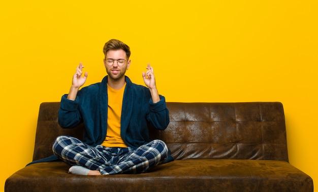 Tragende pyjamas des jungen mannes, die besorgt beide finger kreuzen Premium Fotos