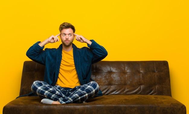 Tragende pyjamas des jungen mannes, die verwirrt glauben oder zweifeln, sich auf eine idee konzentrieren, stark denken und schauen, um raum auf seite zu kopieren Premium Fotos