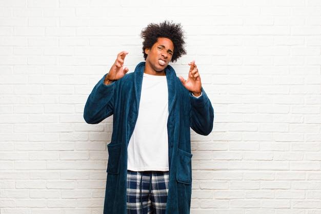 Tragende pyjamas des jungen schwarzen mannes mit dem kleid, das besorgt finger kreuzt und auf gutes glück mit einem besorgten blick gegen ziegelstein hofft Premium Fotos