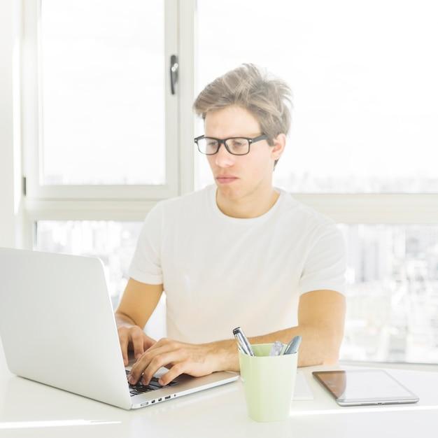 Tragende schauspiele des mannes, die zu hause an laptop arbeiten Kostenlose Fotos