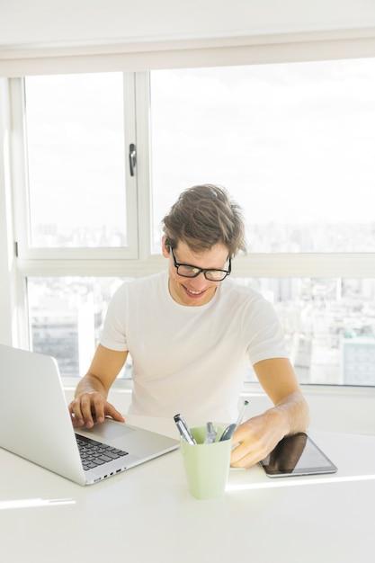 Tragende schauspiele des mittleren erwachsenen mannes, die laptop vor glasfenster verwenden Kostenlose Fotos