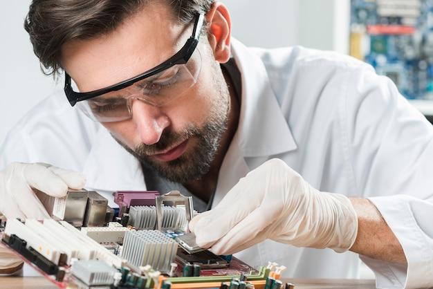 Tragende sicherheitsgläser des jungen männlichen technikers, die chip in computermotherboard einsetzen Premium Fotos