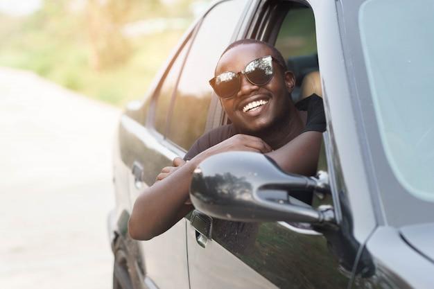 Tragende sonnenbrille des afrikanischen mannfahrers und lächeln beim sitzen in einem auto mit offenem vorderfenster. Premium Fotos