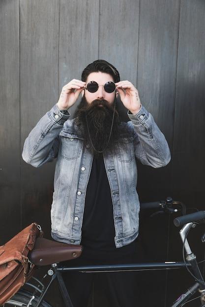 Tragende sonnenbrille des gutaussehenden mannes, die nahes fahrrad steht Kostenlose Fotos