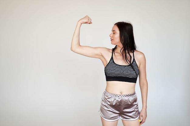 Tragende sportspitze und -schlüpfer starker vorbildlicher sportlicher dünner dame, die das demonstrieren von waffenmuskeln auf weißem hintergrund mit kopienraum zeigen Premium Fotos