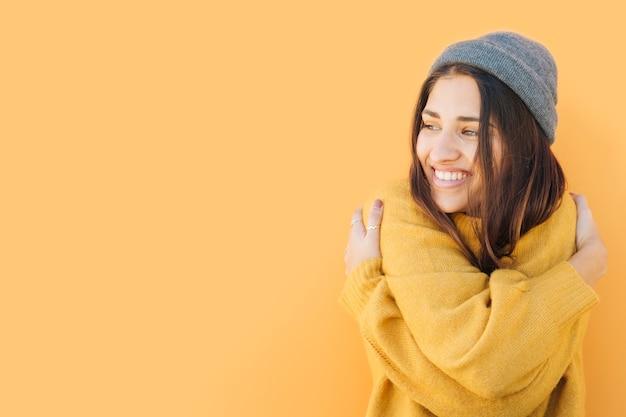 Tragende strickmütze der glücklichen frau, die gegen gelben hintergrund sich umarmt Kostenlose Fotos