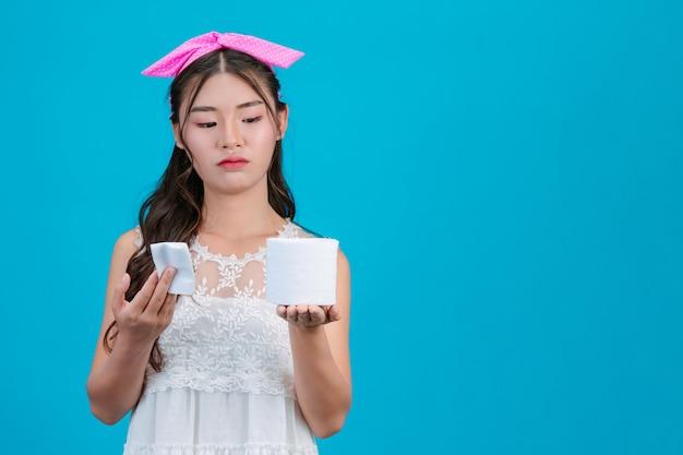 Tragende weiße pyjamas des mädchens, die ein seidenpapier in der hand auf dem blau halten. Kostenlose Fotos