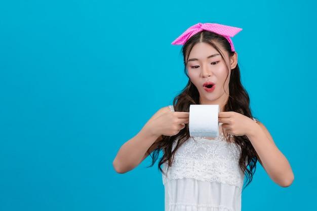 Tragende weiße pyjamas des mädchens, die eine rolle des seidenpapiers in der hand auf dem blau halten. Kostenlose Fotos