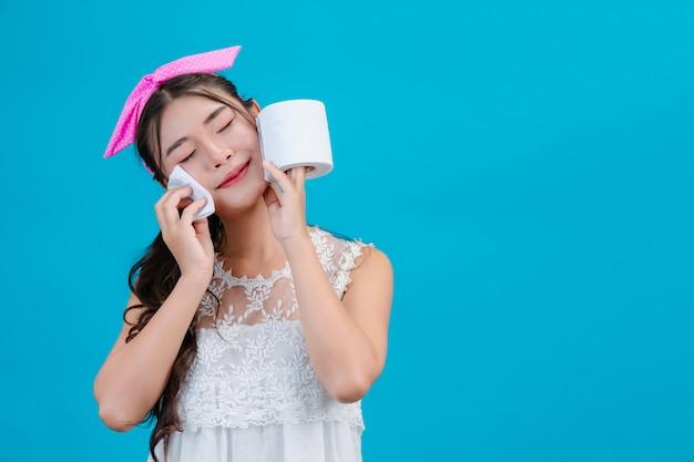 Tragende weiße pyjamas des mädchens unter verwendung des seidenpapiers auf ihrem gesicht auf einem blau. Kostenlose Fotos