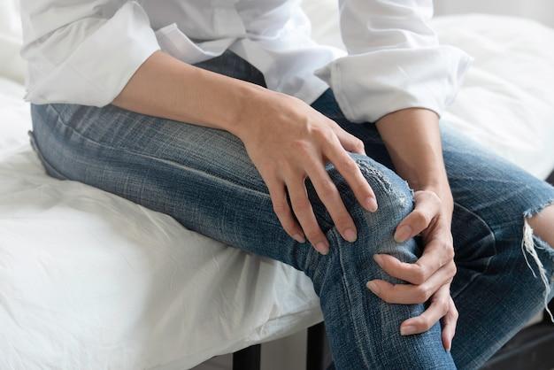 Tragender baumwollstoff der jungen frau, der unter den schmerz im knie leidet. Premium Fotos