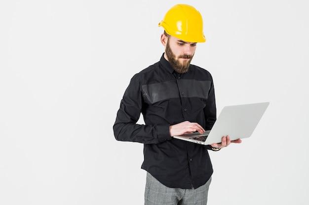 Tragender hardhat des männlichen ingenieurs, der laptop gegen weißen hintergrund verwendet Kostenlose Fotos