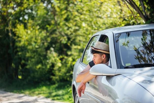 Tragender hut des mannes, der natur durch autofenster schaut Kostenlose Fotos
