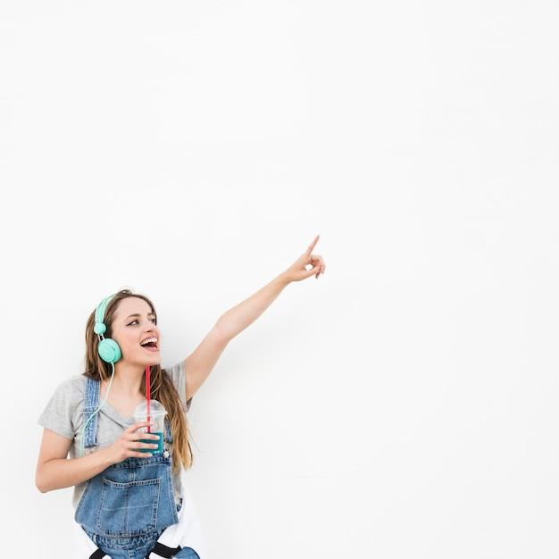 Tragender kopfhörer der frau, der glas saft zeigt finger gegen weißen hintergrund hält Kostenlose Fotos
