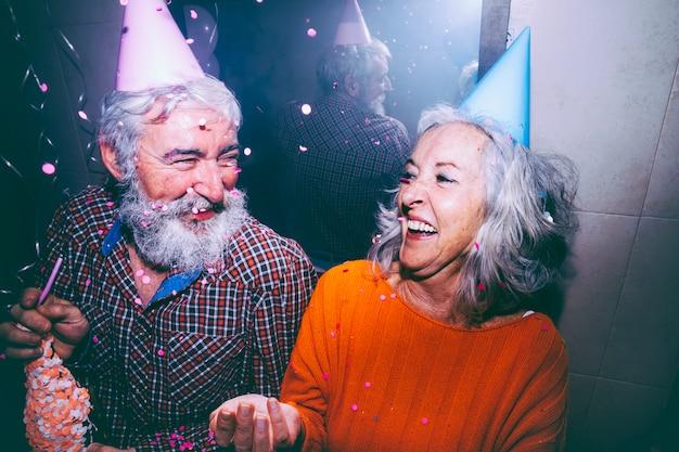Tragender partyhut der älteren paare auf dem kopf, der die geburtstagsfeier genießt Kostenlose Fotos