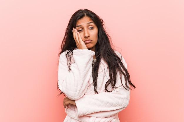 Tragender pyjama der jungen indischen frau, der gelangweilt, ermüdet ist und einen entspannungstag benötigt. Premium Fotos