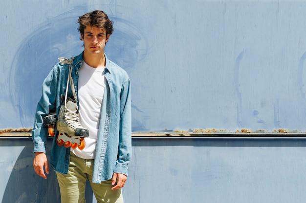 Tragender rollschuh des jungen mannes, der gegen den blauen hintergrund betrachtet kamera steht Kostenlose Fotos