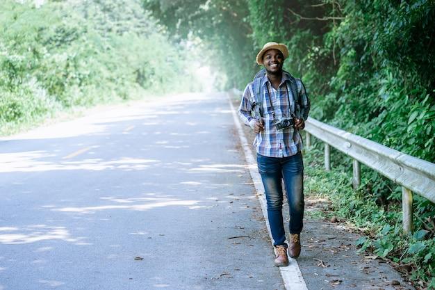 Tragender rucksack der afrikanischen mannreise, der auf der autobahn straße geht Premium Fotos