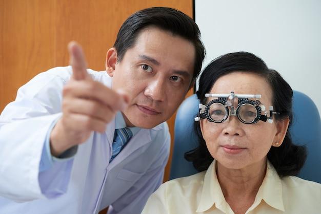 Tragender versuchslinsenrahmen und augenarzt älterer asiatischer dame, die während der sehvermögenüberprüfung zeigen Kostenlose Fotos