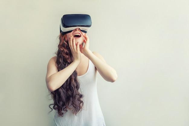 Tragender vr-glaskopfhörer der virtuellen realität der jungen frau des lächelns lokalisiert auf weiß Premium Fotos