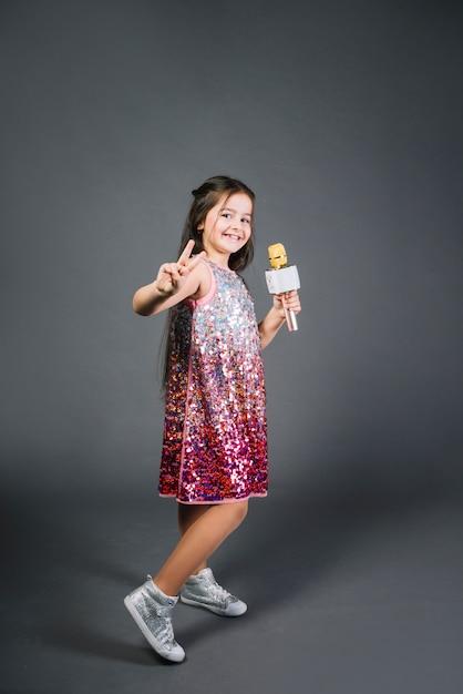 Tragendes paillettenkleid des mädchens, das das mikrofon zeigt siegzeichen gegen grauen hintergrund hält Kostenlose Fotos
