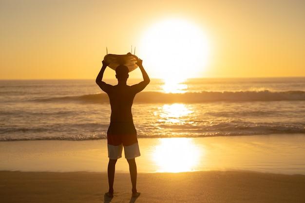 Tragendes surfbrett des mannes auf seinem kopf am strand Kostenlose Fotos