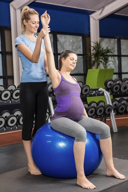 Trainer, der der schwangeren frau trainiert auf einem übungsball an der turnhalle hilft Premium Fotos