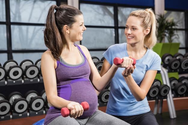 Trainer, der schwangerer frau an der turnhalle mit dummkopf hilft Premium Fotos