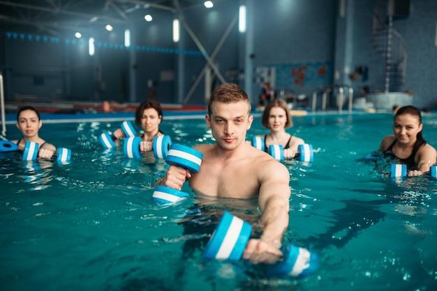 Trainer und weibliche aqua-aerobic-gruppe, übung mit hanteln beim training im schwimmbad. fitnesstraining, wassersport Premium Fotos