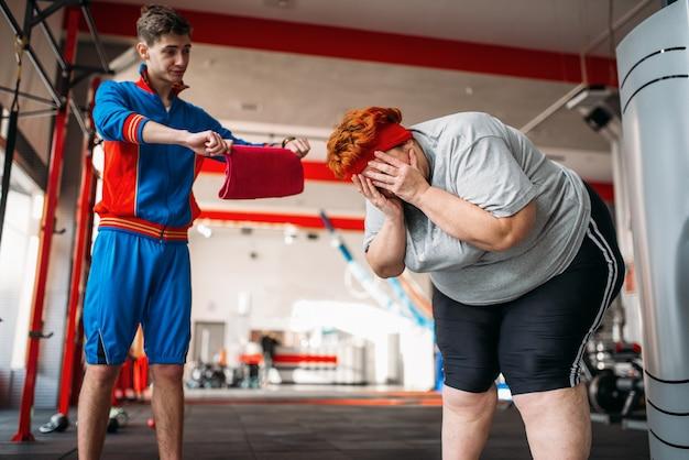 Trainer zwingt übergewichtige frau zu trainieren, hartes training im fitnessstudio. Premium Fotos