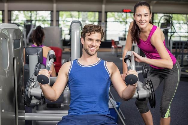 Trainerfrau, die athletischem mann in der turnhalle hilft Premium Fotos