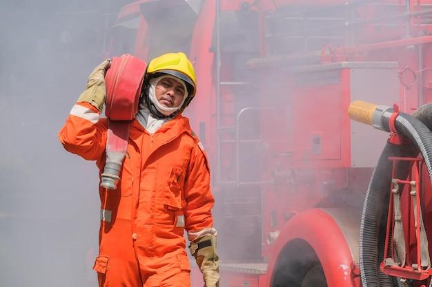 Training der feuerwehrmänner, teamübungen zur brandbekämpfung in notsituationen. ein feuerwehrmann trägt einen wasserschlauch durch die flamme Premium Fotos
